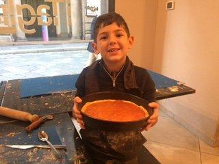 un bambino che sorride con una crostata  marmellata in mano