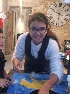 una ragazza che sorride mentre lavora con la pasta fresca