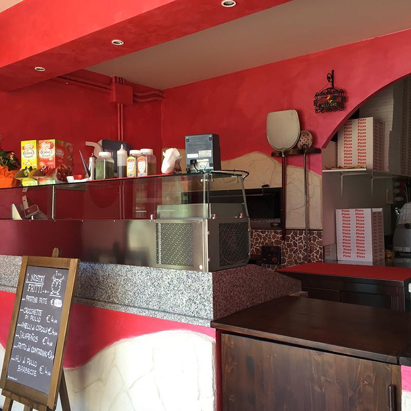 vista del bancone della pizzeria con una vetrina, sopra degli oggetti, delle salse,sotto una lavagna con il menù e vista del forno con accanto dei cartoni per la pizza d'asporto