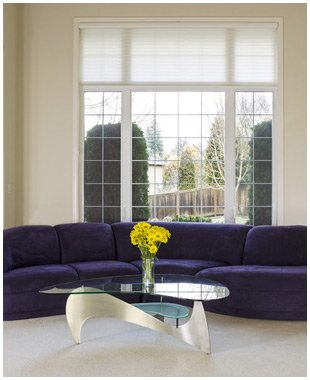 A large purple sofa in front of a large window