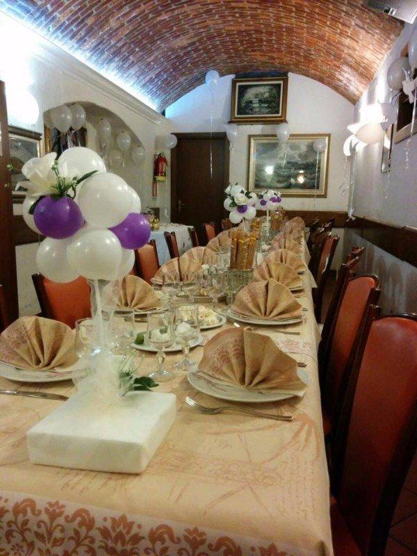 un tavolo lungo apparecchiato e decorato con dei palloncini di color bianco e viola