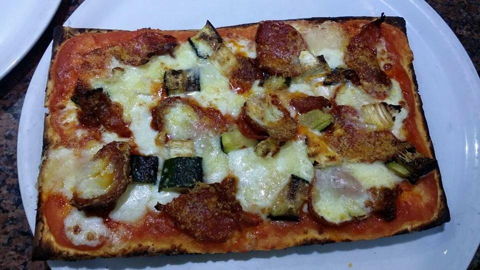 un trancio di pizza con zucchine e fette di salame