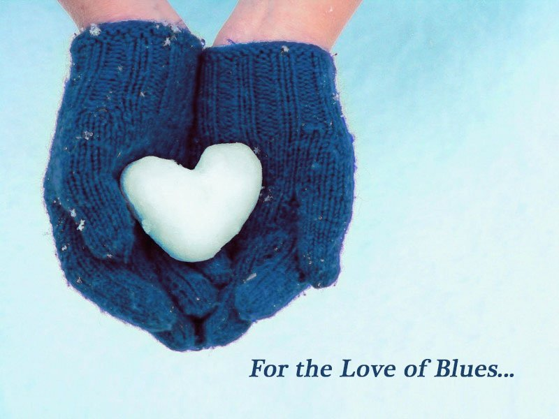Heart shaped snowball in blue gloves