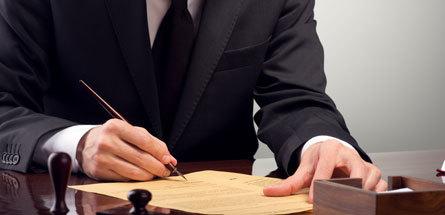 man in suite signing paperwork