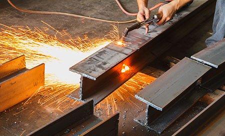 Taglierina in metallo, taglio in acciaio con torcia in acetilene, lavoratore industriale in zona produttiva.