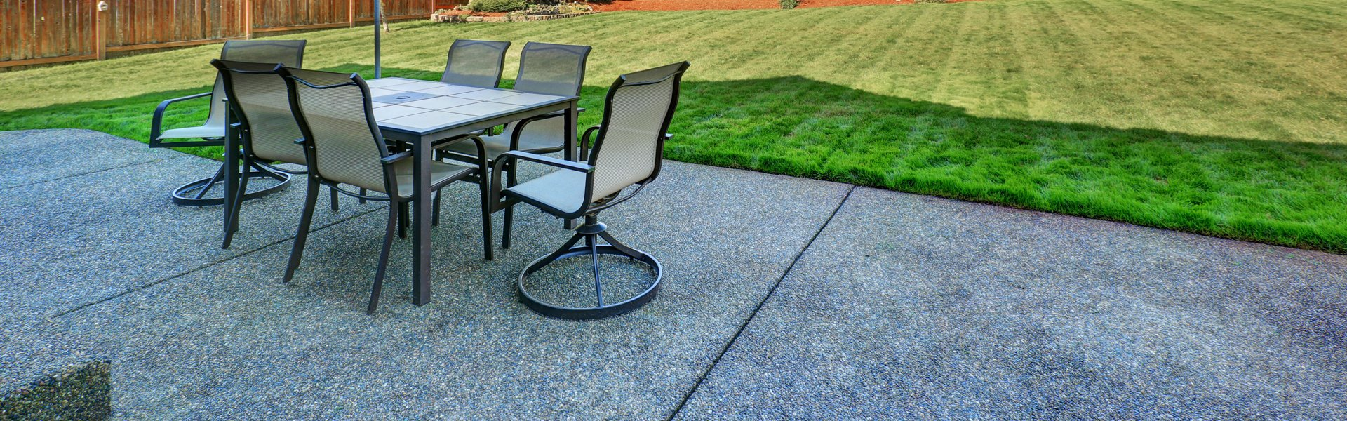 Outdoor dining furniture on a patio beside a striped lawn