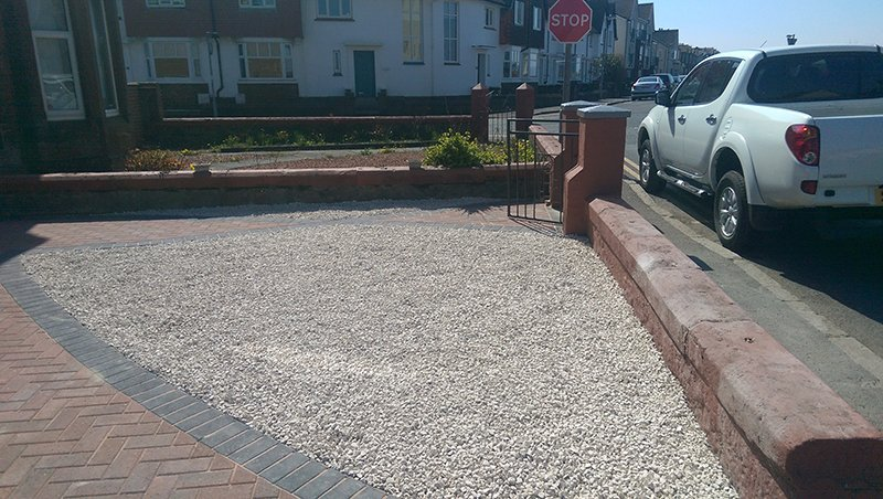 Triangular gravel area surrounded by low brick wall