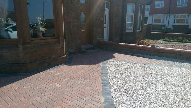 Gravel area edged with paving outside the front door of a house