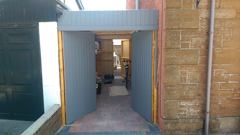 Grey double doors opening onto a yard