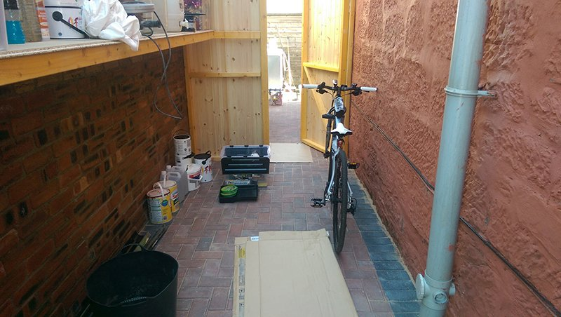 A bike and some paint pots and tools in a shed with timber doors