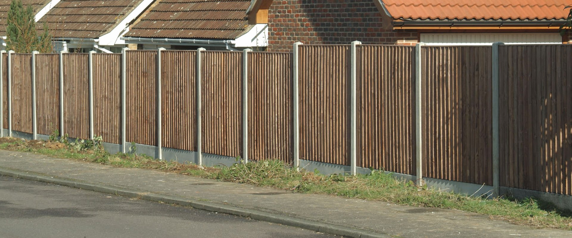 A long wooden fence with concrete posts alongside a pavement