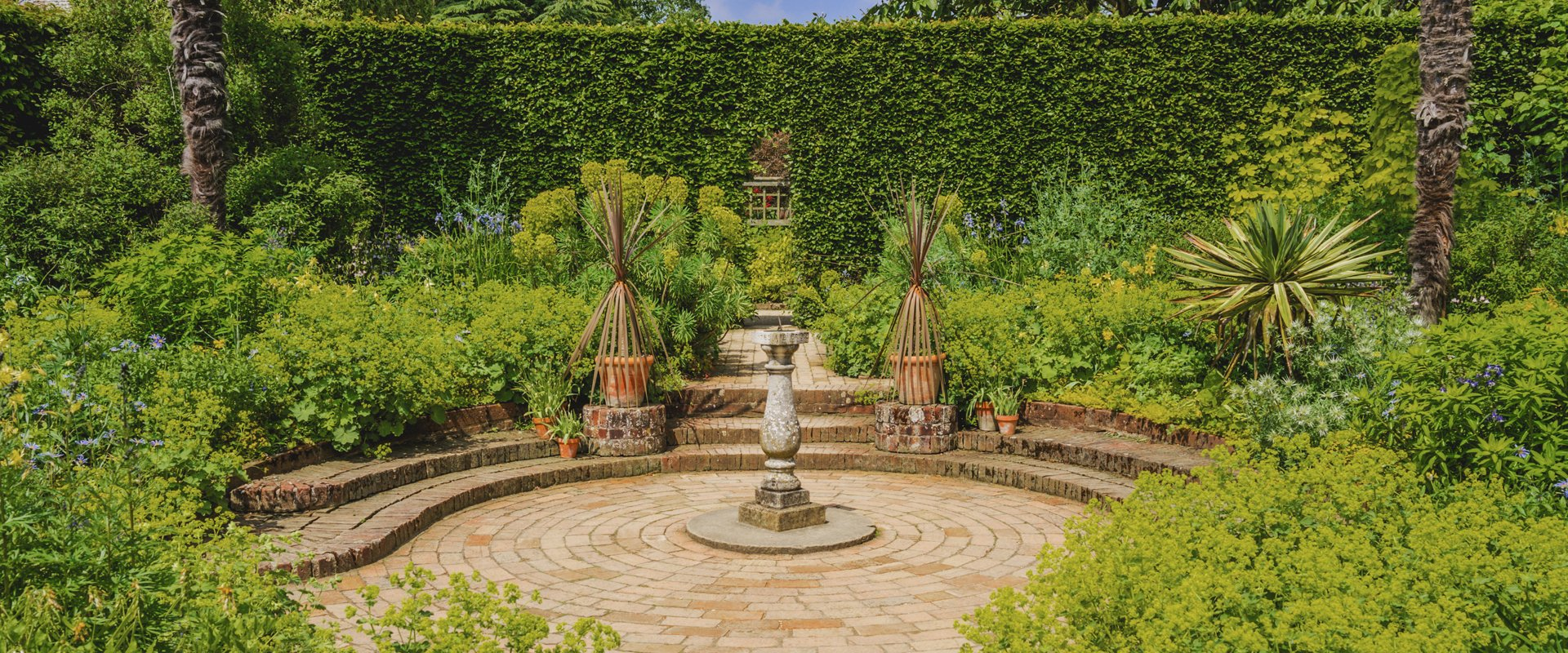 Shrubs and hedges around a paved circular area with stone sundial