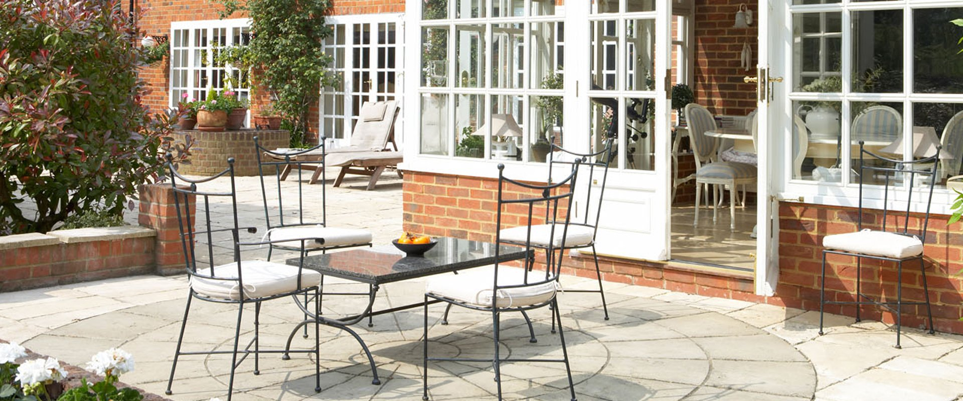 Outdoor dining furniture and loungers on a large patio outside a white conservatory