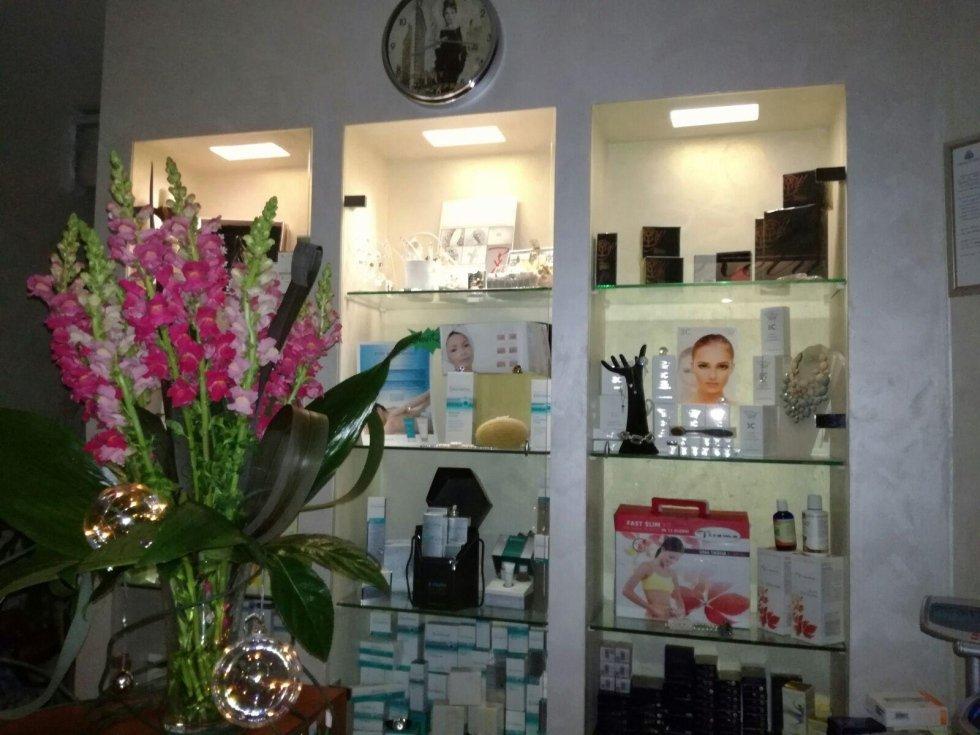una vetrina con dei prodotti e un vaso di fiori fucsia