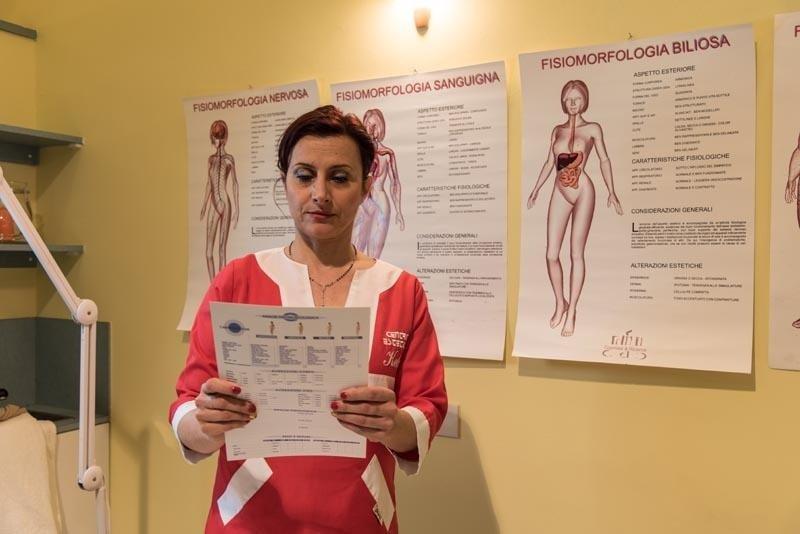 una donna con un camice rosso e bianco e un foglio in mano