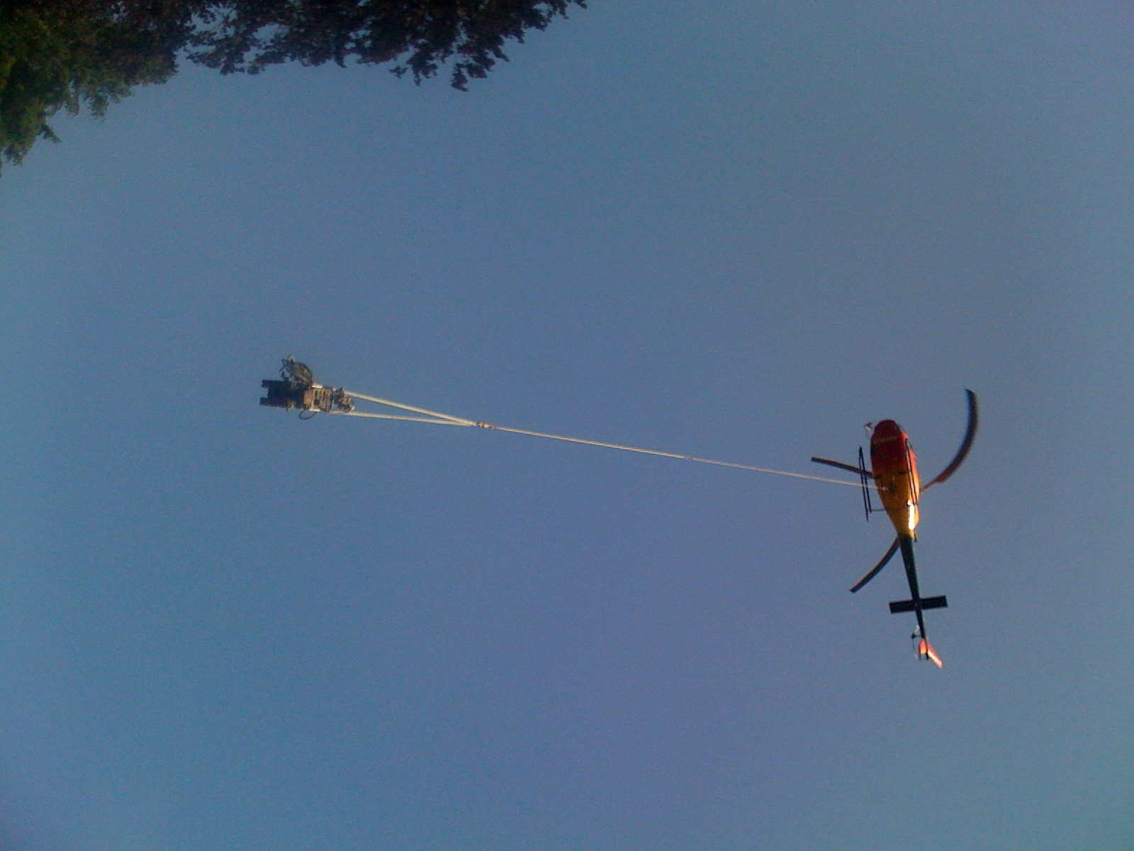 Elicottero in volo trasporta un macchinario