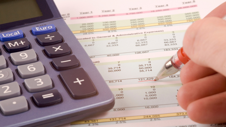 Man with calculator doing accountancy services paperwork in Russellville, AR