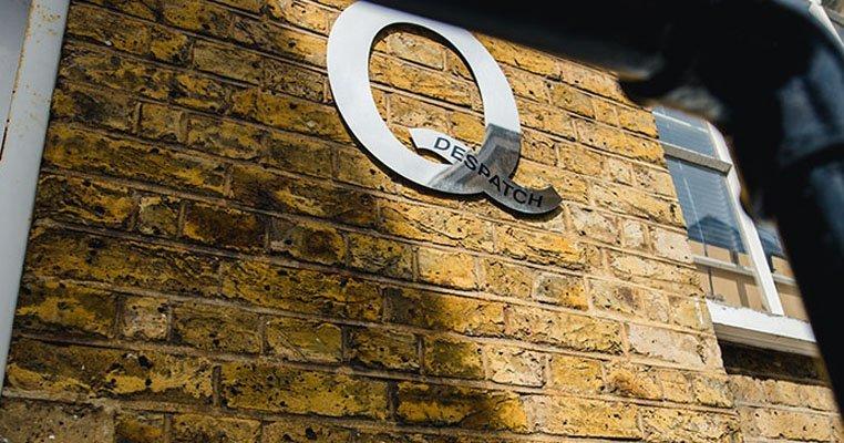 Q Despatch logo on a wall