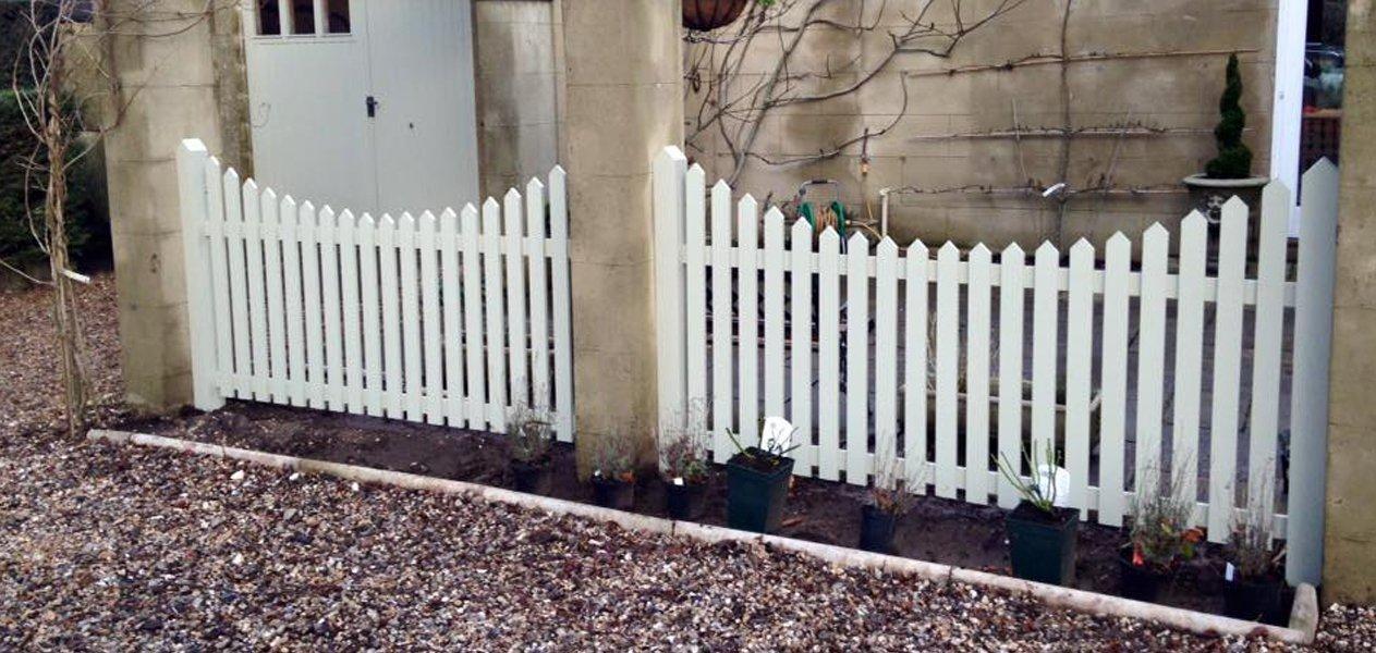 White picket fence next to gravel border