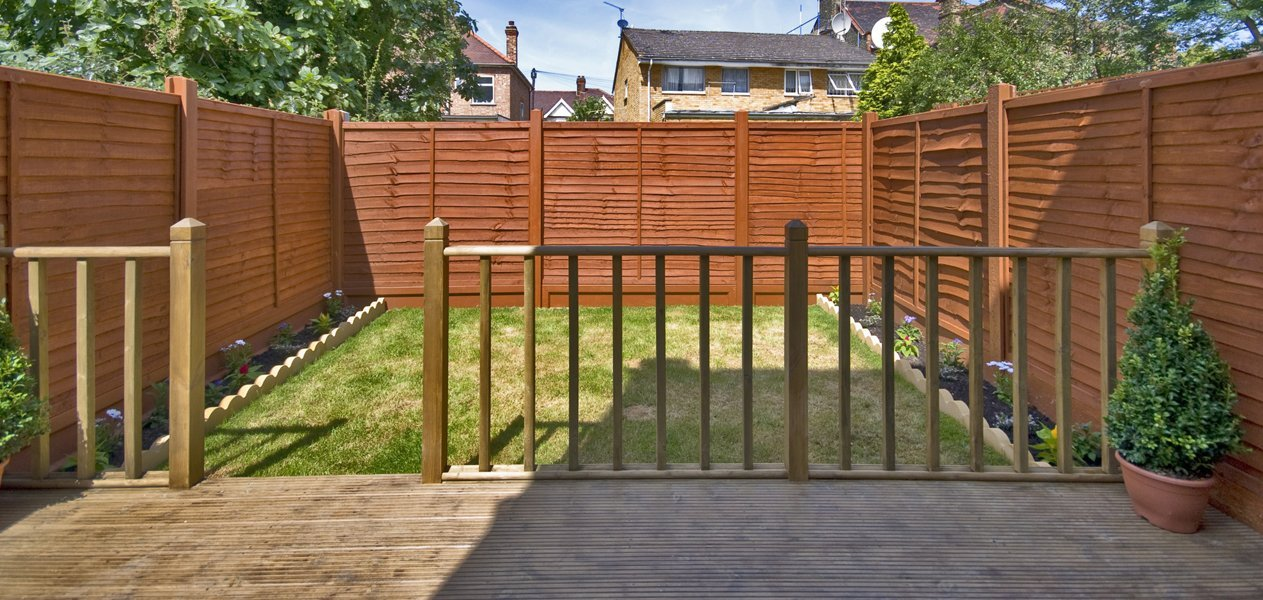 fenced garden with decking and wooden balustrade