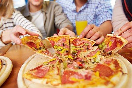 delle persone che prendono delle fette di pizza da un tagliere