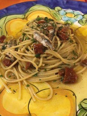 degli spaghetti alle sarde con pomodorini