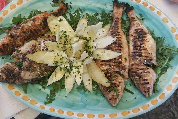 un piatto a base di pesce grigliato con patate e prezzemolo