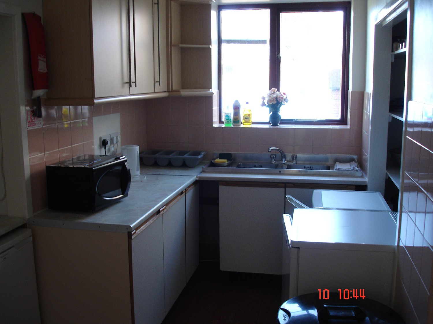 small kitchen with microwave machine , sink and window