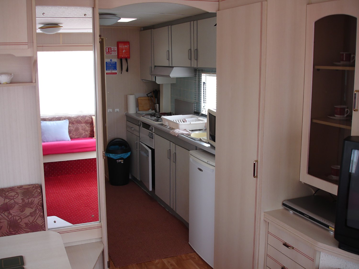 inside view of a caravan with tv, and a kitchen space