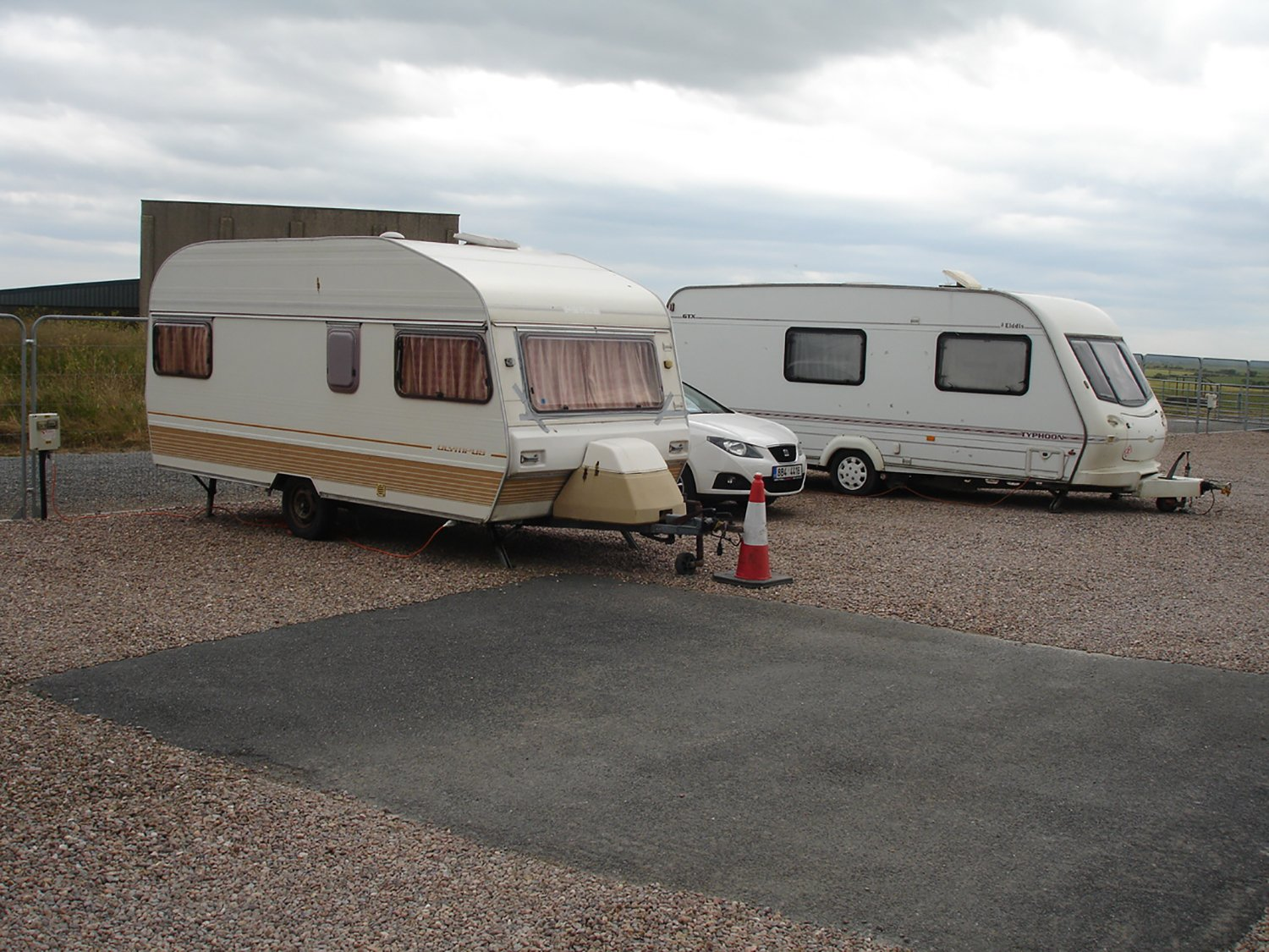 2 caravans and a car in a empty parking lot