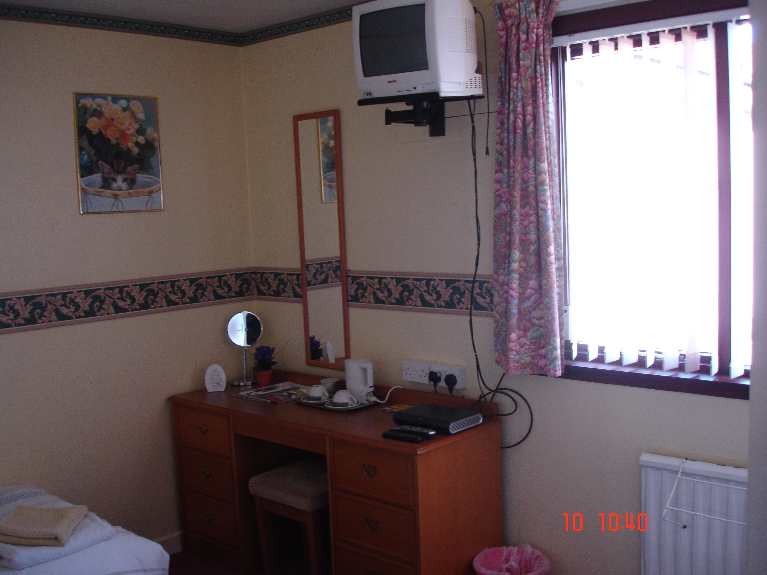 a room with window ,desk , mirror and paintings