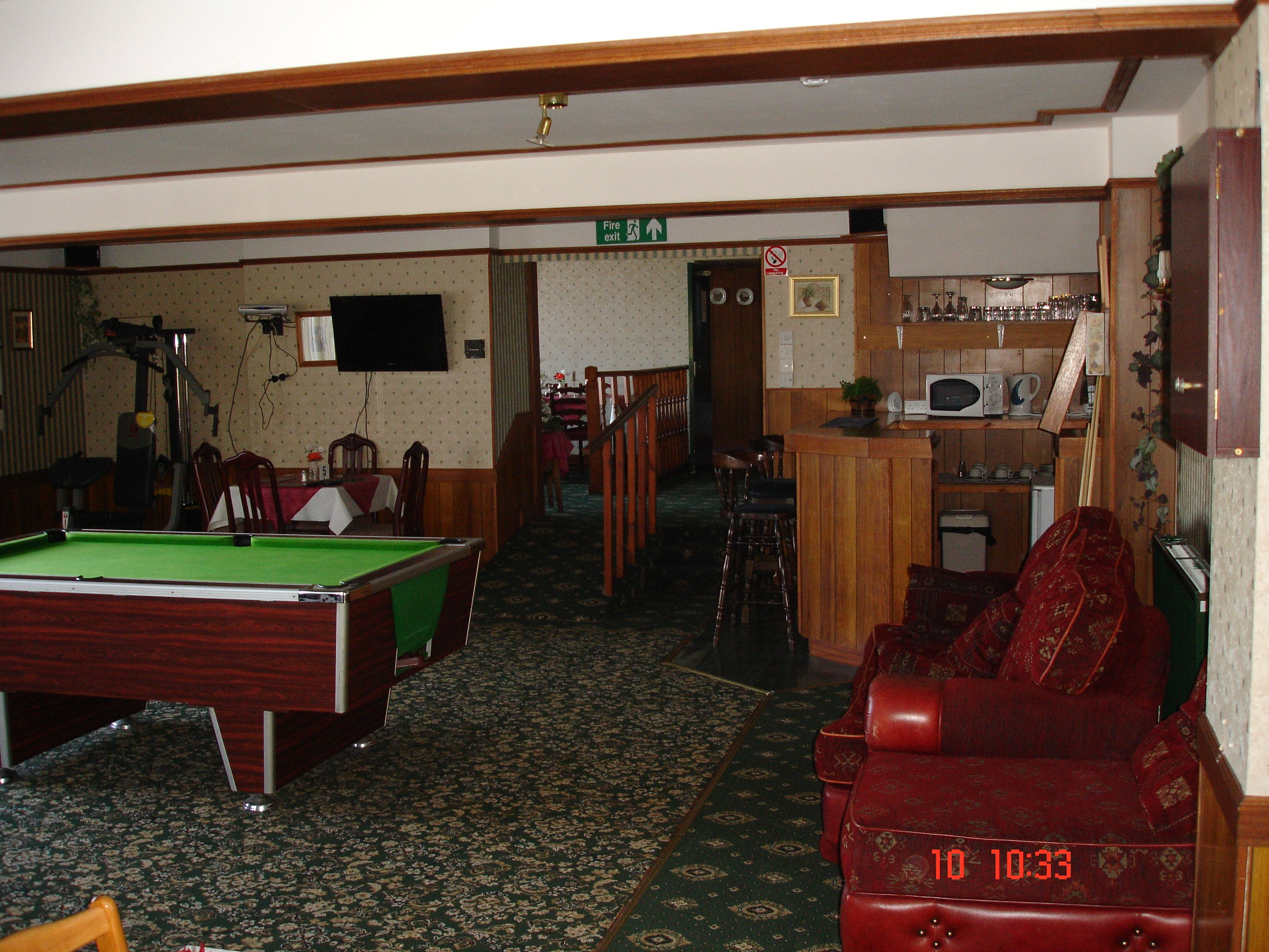 large room with a muscles machine and a pool table in the middle