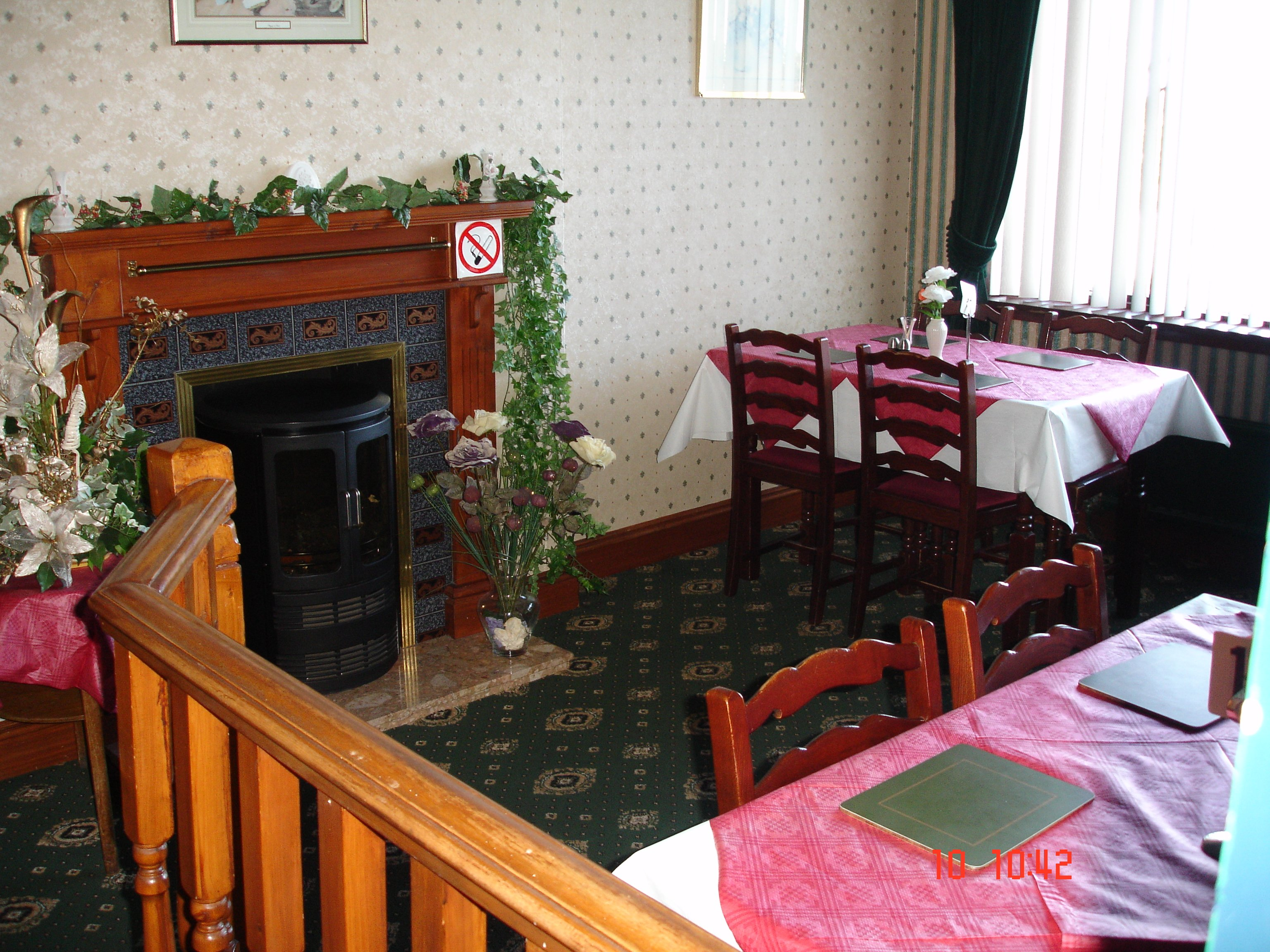 the dining room with multiple tables and chairs and a fireplace
