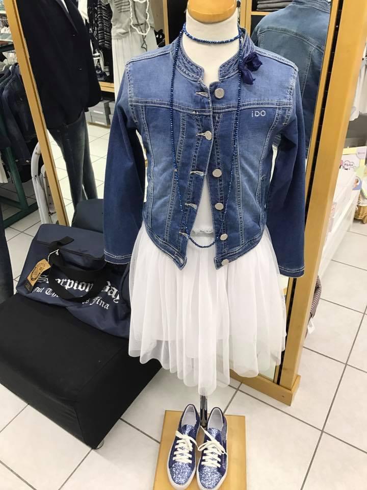 una camicetta di jeans, dei pantaloni di color marrone e delle scarpe grigie e blu scure
