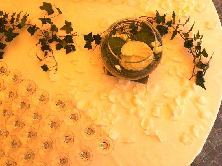 il tavolo rotondo con dei bicchieri dell'edera e dei petali