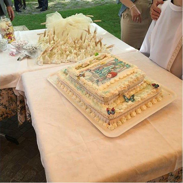 una torta e accanto delle bomboniere a sacchetto con delle spighe
