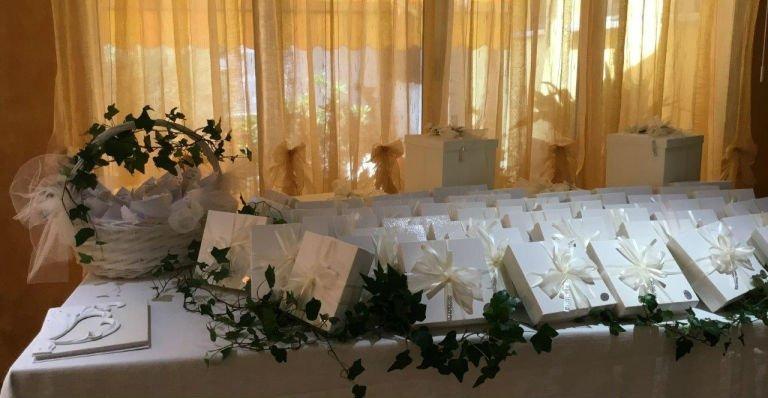 delle confezioni di bomboniere con dei fiocchi bianchi e dell'edera su un tavolo