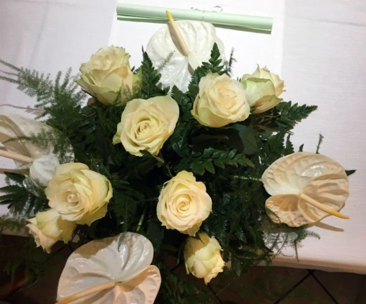 una composizione di rose bianche e fiori