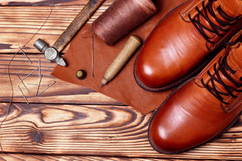 attrezzi da calzolaio e scarpe di pelle su tavolo di legno