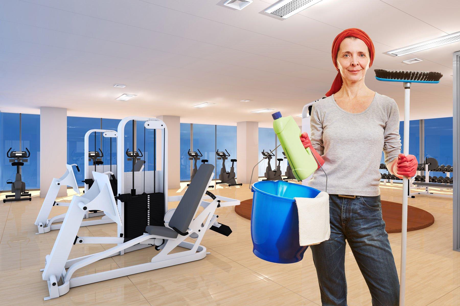 una donna con un secchio- uno spazzolone e altri prodotti per pulizie in una palestra