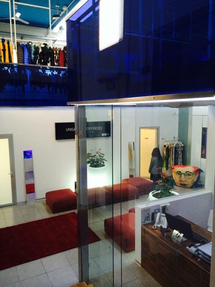 interno dello showroom Ungaro Fashion Agency con cabina-ufficio, divanetti rossi e esposizione di giubbotti di vari colori