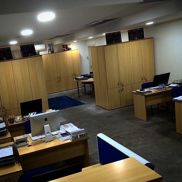 Ufficio con Armadi in legno chiaro scrivanie con computer e tappeti blu
