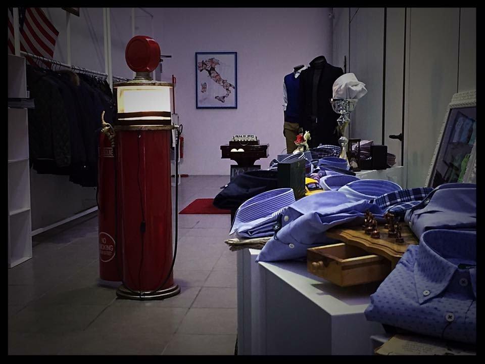 nel negozio, quadro con raffigurazione dell'italia, lampione rosso e camicie dalle sfumature blu esposte