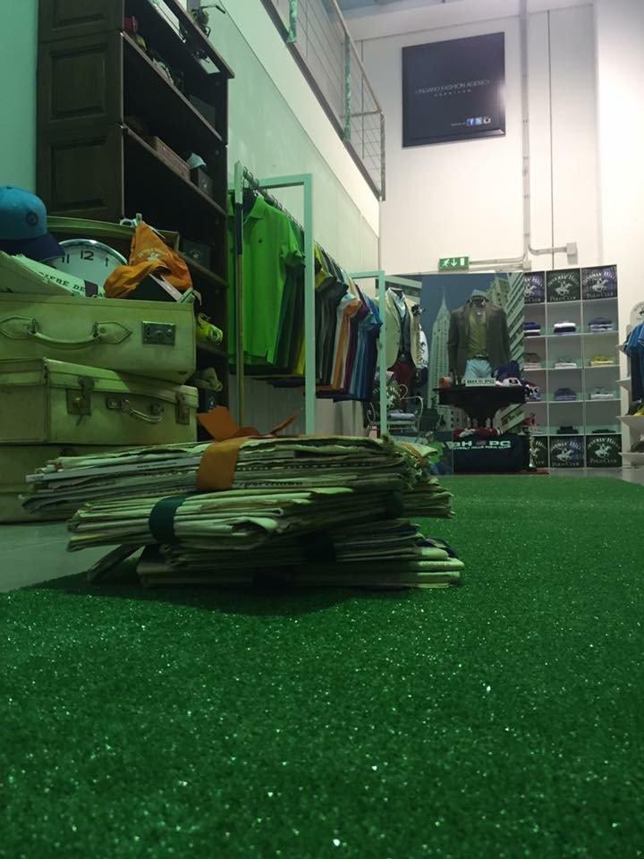 all'interno del negozio, tappeto verde valigie bianche vecchio stile, giornali e magliette polo di vari colori appese