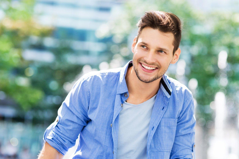 uomo vestito in modo casual sorride guardando in alto