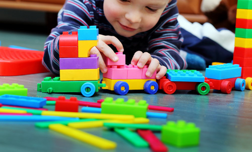 Child making a train with blocks in Daycare in Lincoln, NE
