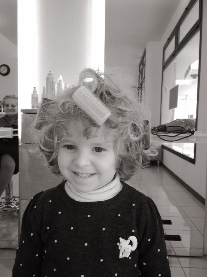bambina con bigodini in testa mentre sorride