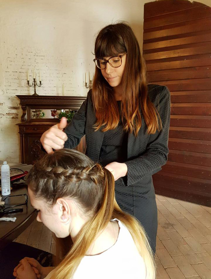 parrucchiera mentre fa la treccia a una cliente