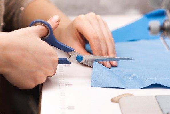 una mano mentre taglia della stoffa con delle forbici