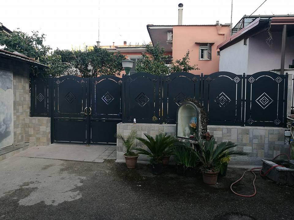 Porta di ferro e palizzata protettiva di metallo circondando il perimetro della casa